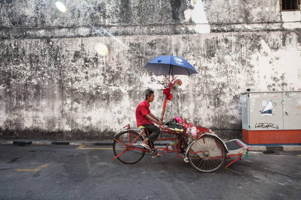 Cycle rickshaw rides down the street in George Town