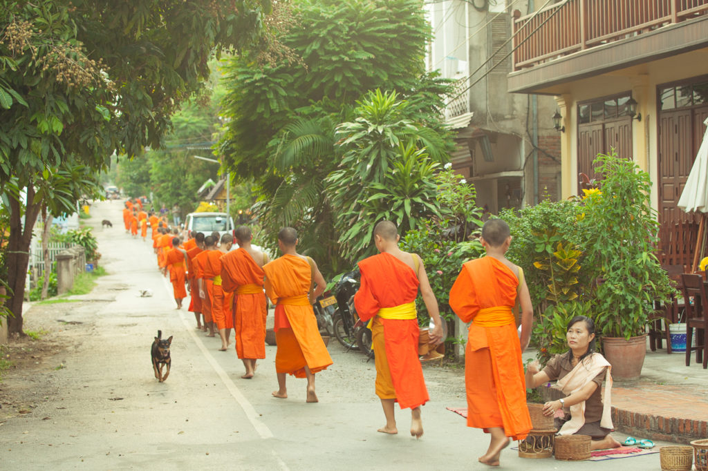 A procession of monks at a street of Luang Prabang, Laos
