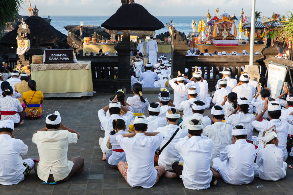 Balinese people pray in the temple during religious ceremony, Tanah Lot, Bali, Indonesia